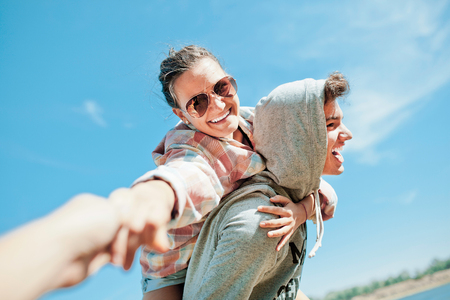 Happy loving couple. Happy young man piggybacking his girlfriend. Cheerful laughing hipsters on blue sky background