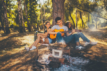 Happy friends in the park having picnic. Group of hipster teen people playing guitar by bonfire on autumn day