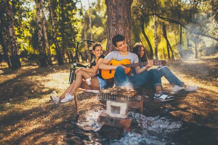 Amigos felizes no parque que tem o piquenique. Grupo de adolescentes moderno as pessoas que jogam a guitarra pela fogueira no dia do outono