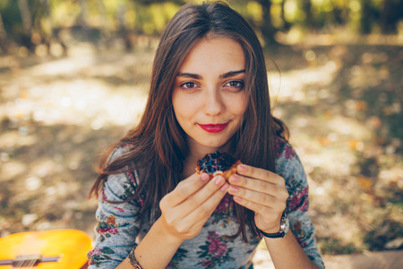 Closeup of beautiful teenage girl holding a tartatel with berries outdoors. Cute hipster brunette young woman on autumn day Banco de Imagens