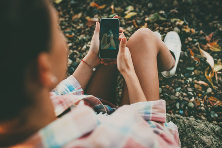 Hipster girl holding a smartphone outdoors. Young woman taking a feet selfie on rocky background on autumn day.