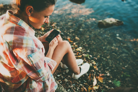 Teenage girl wearing casual clothes holding a smartphone and sitting by a lake. Girl holding a phone outdoors.