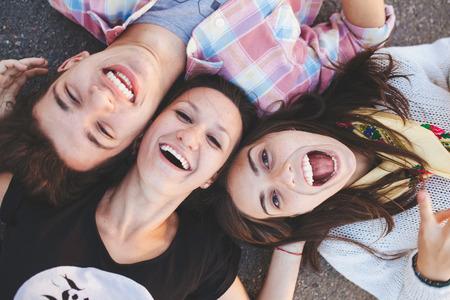 横になっていると笑っている 3 人の親友のクローズ アップ。10 代の人々 が笑みを浮かべてカジュアルな服を着てします。トップ ビュー 写真素材