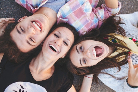 Closeup of three best friends lying down and laughing. Teenage people wearing casual clothes smiling. Top view Banco de Imagens