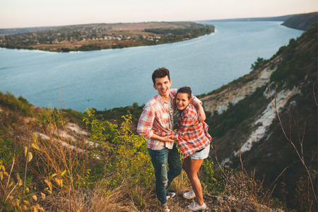 boy lady: Young couple in love outdoor. Portrait of a happy couple hugging on nature with river background. Stock Photo
