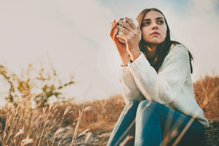 woman serious: Teenage girl sitting alone on autumn cold day. Lonely sad young woman wearing warm sweater. Loneliness and solitude concept. Stock Photo