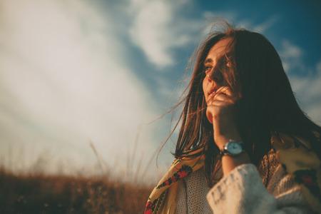 Close-up tiener die in de verte op de herfst koude winderige dag. Knappe jonge vrouw die warme trui denken en aarzelend op hemel achtergrond. Stockfoto