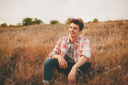 Handsome teenage boy wearing casual shirt sitting on grass on autumn day. Happy smiling young man sitting outdoors.
