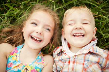 Top view portrait of two happy smiling kids lying on green grass. Cheerful brother and sister laughing together.