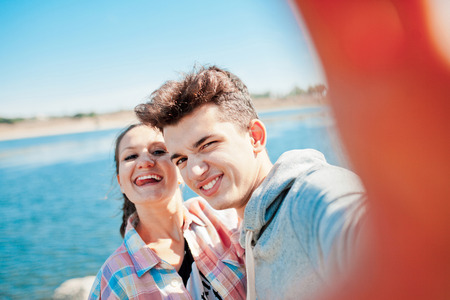 love pic: Young couple making a selfie outdoors and playing ape. Teenage girl and young man having fun with camera on a sunny day
