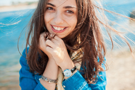 Солнечная портрет застенчивая девушка, глядя на камеру с видом на озеро фоне. Девушка держит руки на лице, потому что скромность
