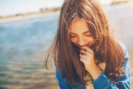 Verlegen meisje schuren op zoek naar beneden. Leuke tiener die verlegen op het meer achtergrond. Film effect. Stockfoto