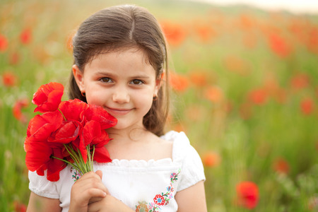 red grass: Close up of cute girl in poppy field holding flowers bouquet. Girl in poppies. Happy kid with poppies.