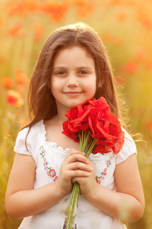 Close up of cute girl in poppy field holding flowers bouquet. Adorable little girl in poppies outdoors. Happy kid with poppies.
