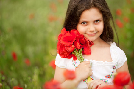 Close up of cute girl in poppy field holding flowers bouquet outdoors. Girl in poppies. Happy kid with poppies.