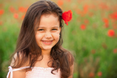 Adorable little girl in poppies. Beautiful smiling child outdoors in a fleld. Shy girl posing for camera in a meadow.