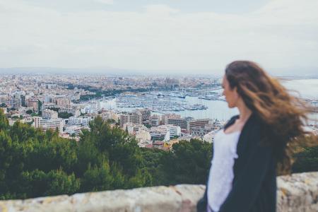 persona pensando: Mujer mirando hacia abajo en la ciudad de Palma, en Mallorca. Vista posterior de la mujer joven de pie en el punto de vista sobre el puerto de la ciudad.