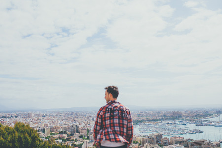 Back view of sad young man standing in front of city of Palma in Majorca. Lonely young male and a city on background