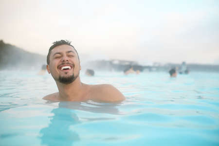 look latino: Laughing hispanic young man relaxing in a pool in Iceland. Happy young man in water.