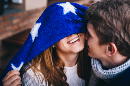 close up eyes: Close up shot of affectionate young couple embracing and kissing outdoors. Beautiful teethy smile of hipster girl hiding her eyes.