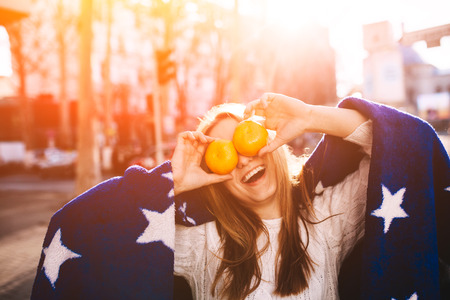 feeling happy: Hipster girl with oranges in her eyes smiling and having fun outdoors. Positive and cheerful young girl