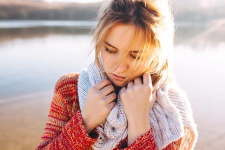 Sad битнику молодая девушка чувство холодной в покое на озере. Один девочка-подросток в холодную погоду.