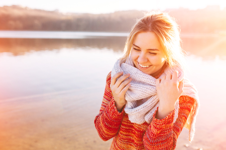portrait of a women: Happy young girl wearing warm clothes standing and smiling by a lake. Sun light at sunset. Stock Photo