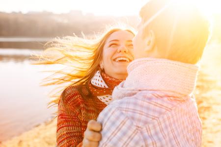 vrouwen: Paar in liefde lachen en plezier bij zonsondergang met zon fakkels