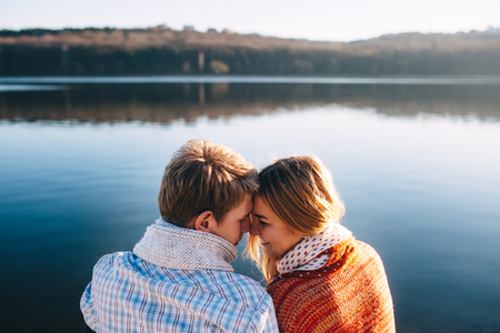 Happy young couple in love wearing warm clothes cuddling at a lake,