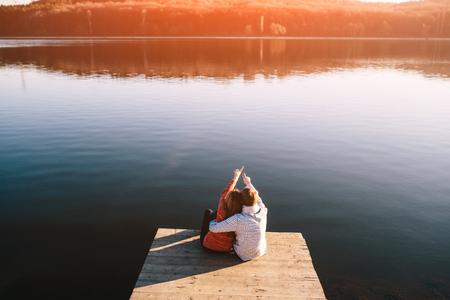 Una joven pareja de adolescentes soñando en el muelle de madera en un lago