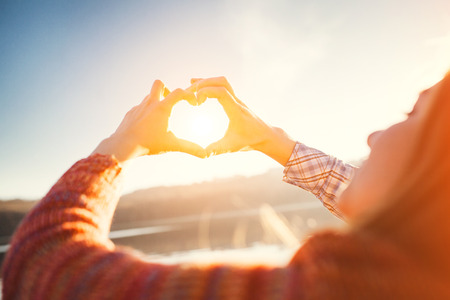 Young people making heart shape of hands. Sun light heart concept. Stock Photo
