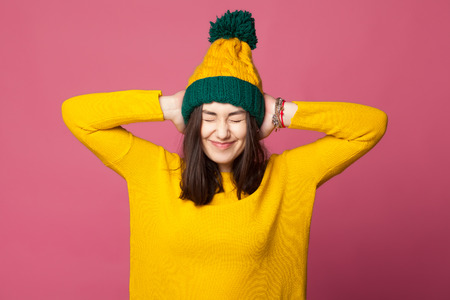 hands covering ears: Young teenager girl closing ears with her hands isolated. Hipster stress. Young girl wearing yellow bright clothes covering ears