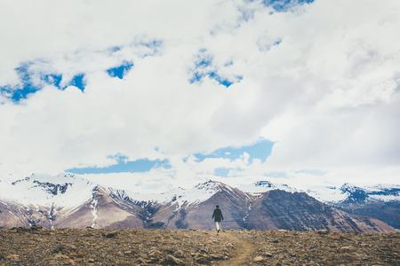 persona caminando: Vista trasera de una mujer joven que camina lejos de las montañas nevadas de Islandia.