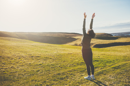 salutation: Silhouette of a young woman doing yoga in Iceland. Girl doing sun salutation on meadow