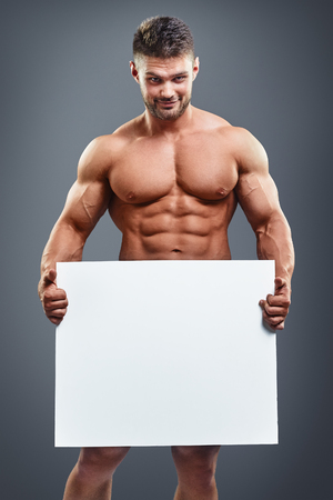 uomo nudo: bodybuilder completa che tiene manifesto in bianco isolato su sfondo grigio. Bel uomo muscoloso che tiene scheda bianca in mano.
