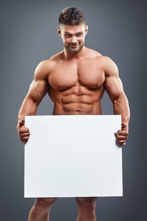 hombre desnudo: culturista cuerpo completo que sostiene el cartel blanco en blanco sobre fondo gris. Hombre muscular hermoso que sostiene la tarjeta blanca en las manos.