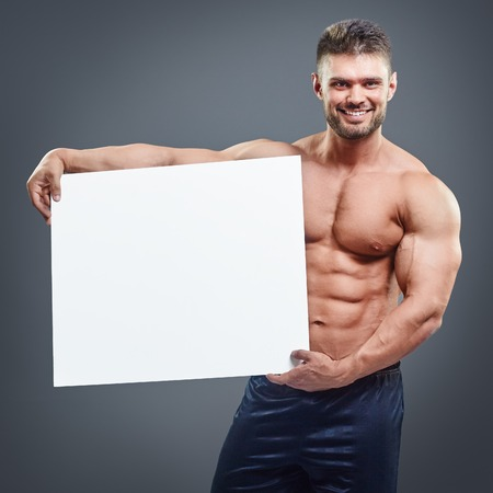 athletic type: Smiling bodybuilder holding blank white poster isolated on gray background. Handsome muscular man holding white board in hands.