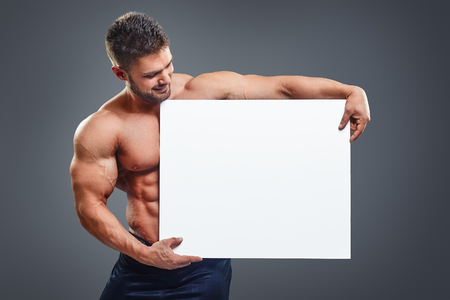 Strong bodybuilder with six pack holding blank white poster isolated on gray background. Handsome muscular man holding and looking at white board in hands.