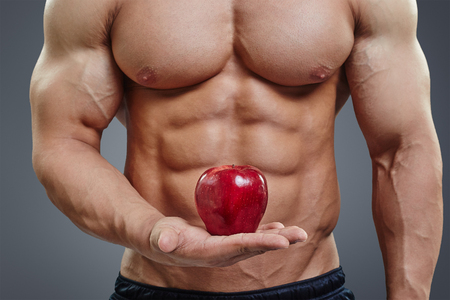 nude abs: Fit man holding a fresh red apple on grey background. Healthy food abstract concept. Shirtless bodybuilder with perfect six pack abs healthy diet concept. Stock Photo