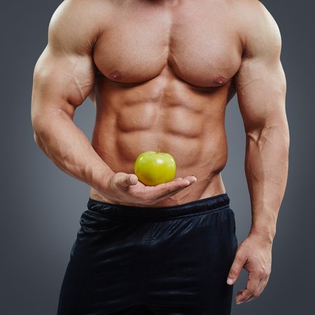 six pack: Shirtless muscular man holding a fresh yellow apple on grey background. Vegetarian diet. Perfect six pack abdominal