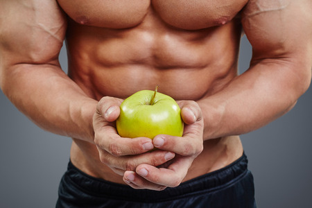 six pack abs: Close up of shirtless bodybuilder holding an apple in his hands. Fit man holding apple on six pack abs background. Healthy diet concept. Stock Photo