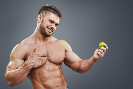 Shirtless muscular man pointing to lime. Healthy food and vitamins abstract concept.  Bodybuilder sport nutrition. Stock Photo