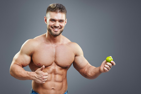 six pack: Fit smiling man holding a fresh lime on grey background. Healthy food abstract concept. Shirtless bodybuilder with perfect six pack abs healthy nutrition and vitamins concept. Stock Photo