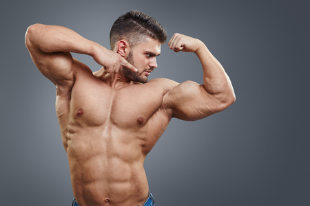 Shirtless muscular athletic man pointing to his strained biceps muscle. Sexy bodybuilder showing his muscular body on grey background with copy space.
