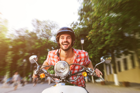 白いスクーターに乗ってハンサムな若い男を笑っています。モーションは、概念をぼやけています。底面図