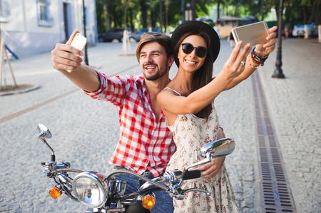 descolados casal de amigos que fazem uma foto selfie. Homem novo da forma e mulher que fazem fotografias com telefone celular na cena urbana ao ar livre no dia de verão.