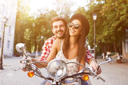 junge nackte frau: Junge und sorglose Paar Lernen einen Roller auf der Straße zu fahren. Junger Mann unterrichtet Hipster Mädchen, das ein Motorrad zu fahren.
