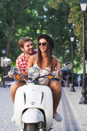 scooter: aprendizaje joven pareja alegre hermosa para montar un scooter blanco de cosecha juntos. Hombre joven que ense�a a su novia inconformista para conducir moto