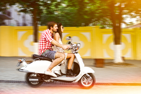 Young and carefree couple learning to drive a scooter on a road. Young man is teaching hipster girl to ride a motorcycle. 版權商用圖片 - 51667825