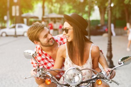 scooter: aprendizaje pareja joven y despreocupada para conducir una moto en una carretera. El hombre joven est� ense�ando chica inconformista para conducir una motocicleta.